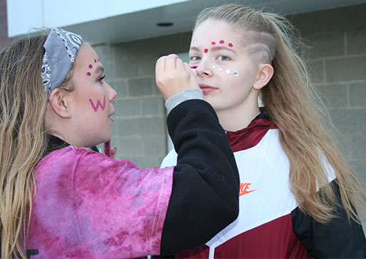 picture of student having face painted by another student