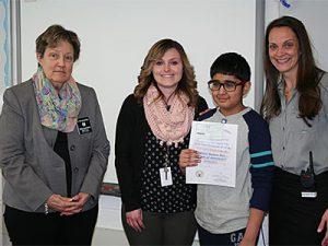 picture of essay winner standing with teacher, school principal and Elks representative