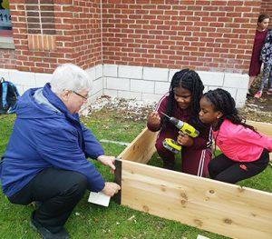 picture of staff volunteer helping students build garden bed