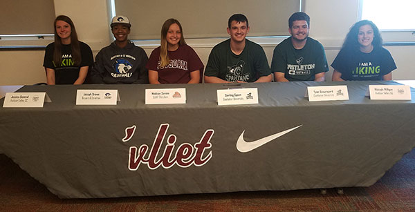 group picture of six student athletes seated at table with WaterVliet athletic banner