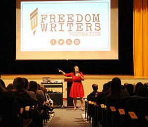 picture of author with microphone in hand addressing the audience