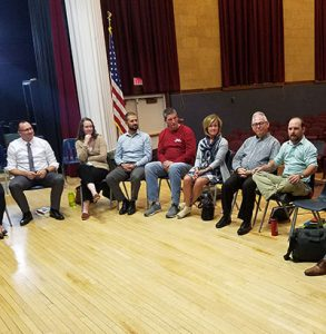 picture of educators seated in circle in auditorium engaged in conversation