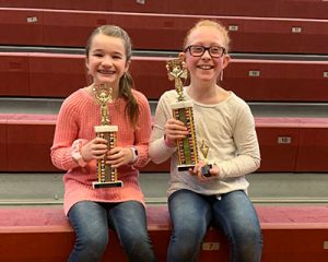 picture of spelling bee champion and runner up holding trophies and smiling