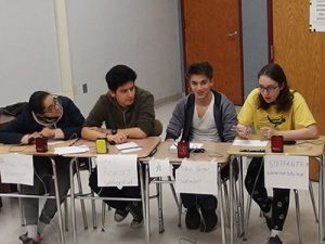 picture of four varsity Masterminds team members seated at desks participating in competition