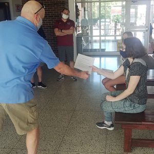 picture of science teacher handing science award scholarship to student seated on bench as high school principal and assistant superintendent stand nearby