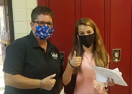 picture of hall monitor wearing face mask assisting student wearing face mask. Both showing thumbs up.
