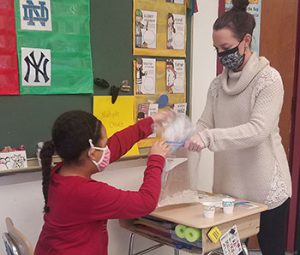 a teacher holds a large plastic bag open as a student places a small bag filled with liquid mixture inside during ice cream making activity