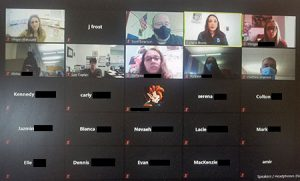 picture of computer screen during Zoom presentation with reporter, students and teachers