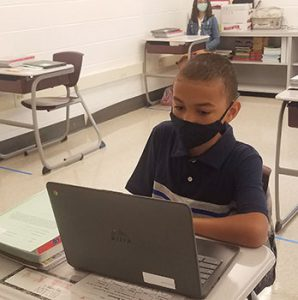 picture of student wearing face mask seated at desk and working on laptop computer