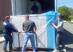 picture of high school maintenance staff loading mattresses onto a cart at the back of a tractor trailer.