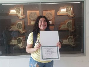 picture of student wearing a mask and holding merit scholarship certificate