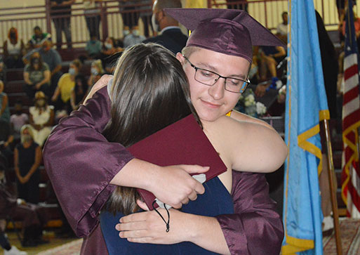 picture of graduate with diploma in hand hugging teacher