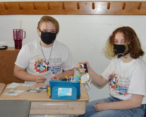 picture of two students at desk working on Lego robot